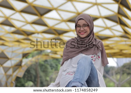 Cute little girl wearing hijab casually as personal style in the morning at the park. #1174858249