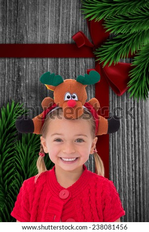 Cute little girl wearing rudolph headband against wood with festive bow