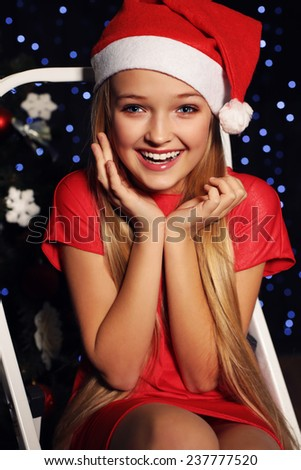 cute little girl whith long blond hair and blue beautiful eyes in santa hat and red suit surprised of Christmas present on the backgroud of holiday shining lights