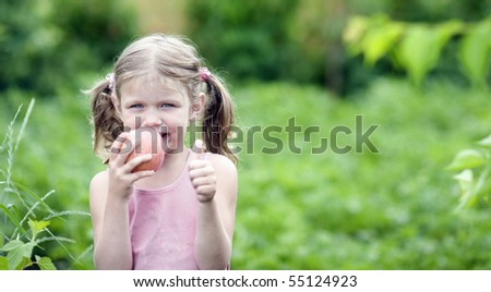 Cute Little girl with a Apple in Her Hand Outdoors.