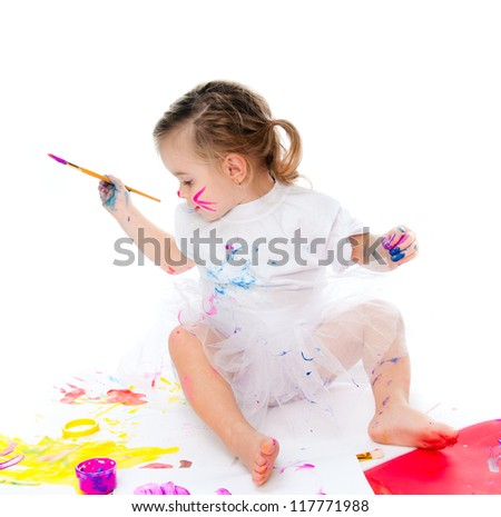 cute little girl with a brush and paints on a white