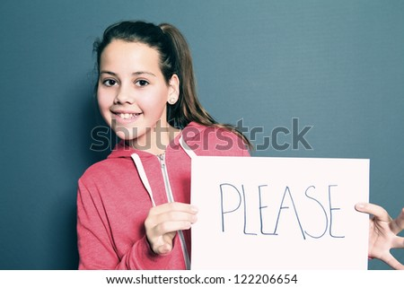 Cute little girl with a happy grin holding up a sheet of white paper with a handwritten note saying PLEASE, studio portrait on grey