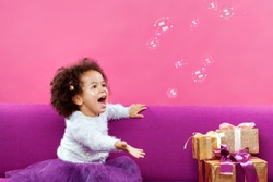 Cute little girl with a lot of gift boxes sitting on sofa and catching soap bubbles against pink background