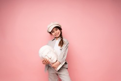 Cute little girl with a pigtail holding a sculpture in the shape of a head standing on a pink background