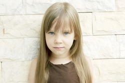 Cute little girl with a serious angry expression, outside, wall background