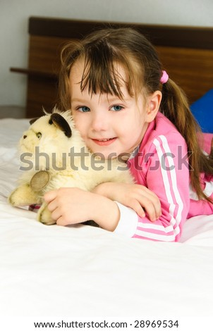 cute little girl with a toy on the bed at home