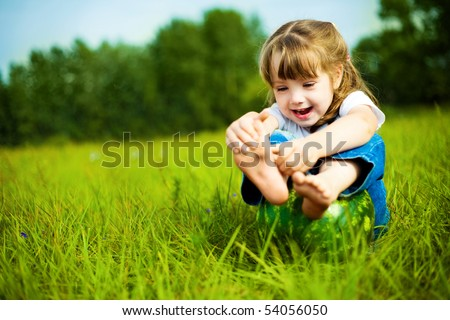 cute little girl with a water-melon on the grass in summertime