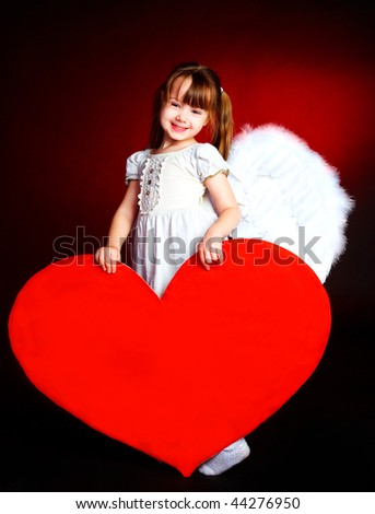 cute little girl with angel wings and a big heart in her hands