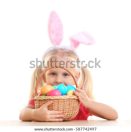 Cute little girl with bunny ears and basket full of Easter eggs on white background #587742497