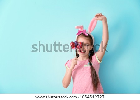 Cute little girl with bunny ears and Easter eggs on color background #1054519727