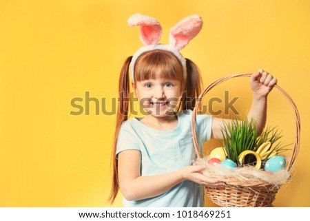 Cute little girl with bunny ears holding basket full of Easter eggs on color background #1018469251