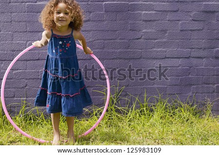 Cute little girl with curly hair posing with her hula hoop in front of a blue brick wall