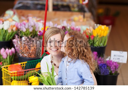 Cute little girl with curly red head kissing her mother as they shop for fresh flowers in a supermarket