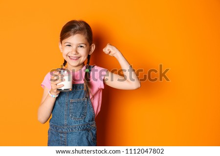 Cute little girl with glass of milk on color background #1112047802