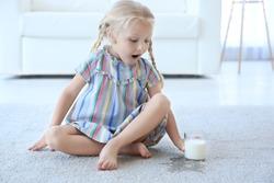 Cute little girl with glass of milk sitting on carpet near wet spot