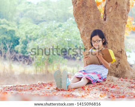 Cute little girl with glasses reading a book under big flower tree