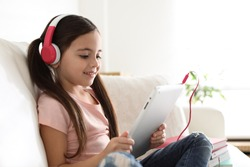 Cute little girl with headphones and tablet listening to audiobook at home