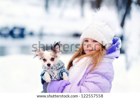 cute little girl with her lovely pets dog chihuahua in winter outdoor
