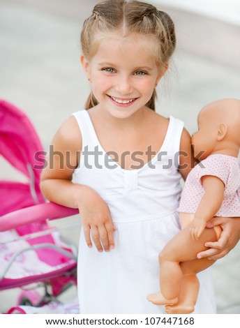 Cute little girl with her toy carriage - stock photo