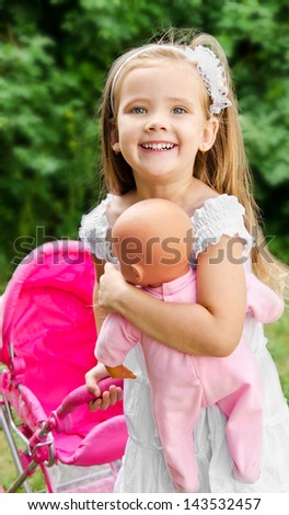 Cute little girl with her toy carriage and doll outdoors
