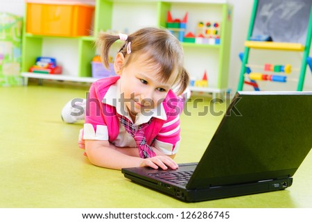 Cute little girl with laptop on floor at home