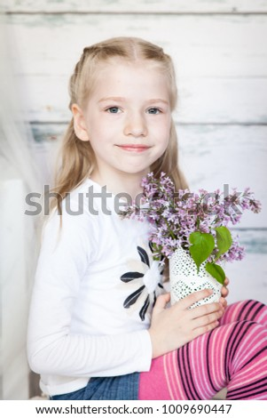 Cute little girl with lilac branch in a vase in a light spring studio #1009690447