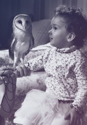 Cute little girl with little barn owl . Vintage style monochrome picture.