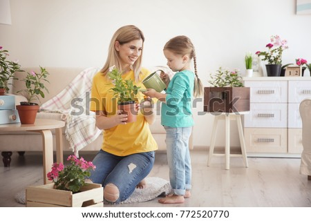 Cute little girl with mother taking care of plants indoors #772520770