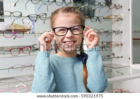 Cute little girl with new glasses in shop #590321975