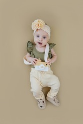 Cute little girl with photo camera. Adorable funny baby girl in stylish clothes  with bow on head and toy photo camera over shoulder lying on brown background