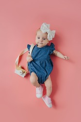 Cute little girl with photo camera. Top view of adorable funny baby girl in stylish bodysuit with bow on head and toy photo camera over shoulder lying on pink background