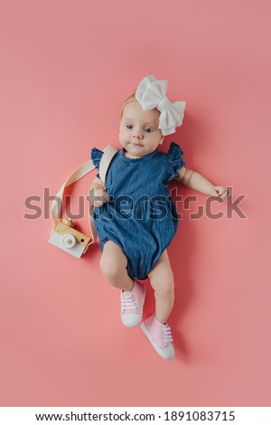 Cute little girl with photo camera. Top view of adorable funny baby girl in stylish bodysuit with bow on head and toy photo camera over shoulder lying on pink background Photo stock ©