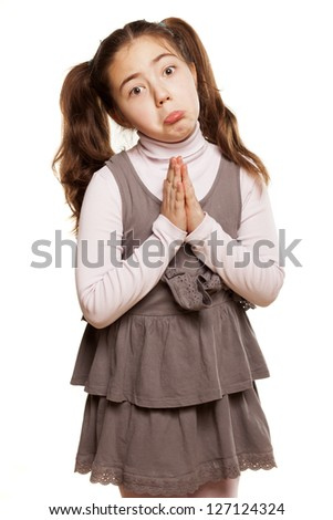 Cute little girl with praying hands on white background