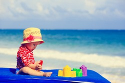 cute little girl  with sand toys on summer beach