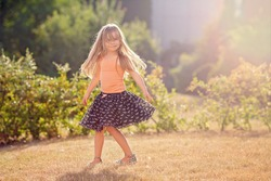 Cute little girl with skirt, dancing and swirling around, summertime outdoors
