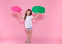 Cute little girl with speech icon on pink background .The concept of communication and communication . Studio shooting