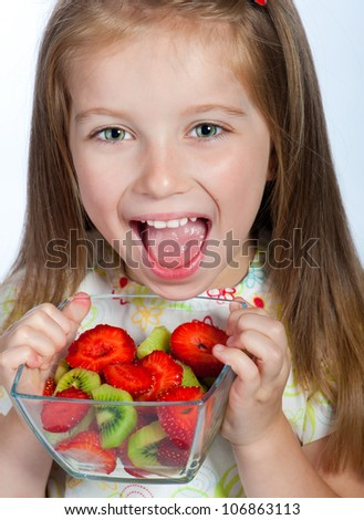 Cute little girl  with the  fruit salad on a white background