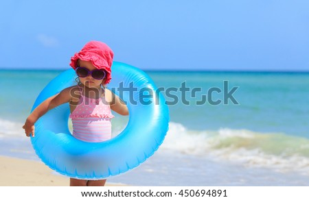 cute little girl with toy floating ring at beach #450694891