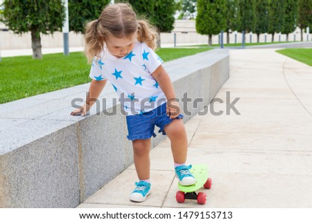 Cute little girl with two tails learns to skate to skateboard on a Sunny summer day. Active healthy leisure and outdoor sport for kids. Fun activity for kid.
