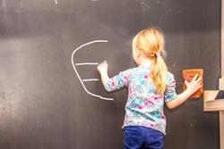 Cute little girl writing Euro sign on chalkboard in a classroom