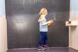 Cute little girl writing on chalkboard in a classroom