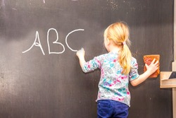 Cute little girl writing on chalkboard in a classroom