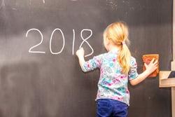 Cute little girl writing 2018 on chalkboard in a classroom