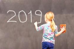 Cute little girl writing 2019 on chalkboard in a classroom