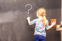 Cute little girl writing question mark on chalkboard in a classroom