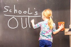 Cute little girl writing Schools's out on chalkboard in a classroom
