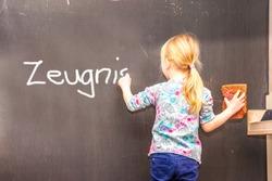 Cute little girl writing Zeugnis on chalkboard in a classroom - Translation Testimony