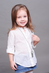 Cute little girl 4-5 year old posing over gray in studio. Wearing stylish shirt and skirt. Smiling child. Childhood.
