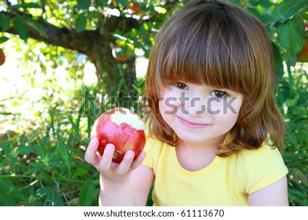 Cute little girls eating red delicious apple