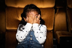 Cute little girls sit and watch fun movies in a thrilling cinema with horror and thrilling, using hands to cover their faces, leaving only the eyes to want to thrill.